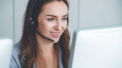 woman wearing headset looking at computer live engagement
